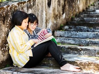 Two little girls with glasses reading a book