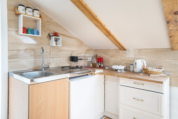 Interior of a kitchen in a private studio in mansard