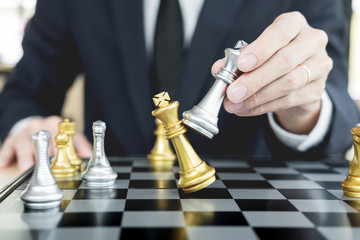 businessman playing  chess figure take a checkmate another king with team, strategy or management win or success concept.