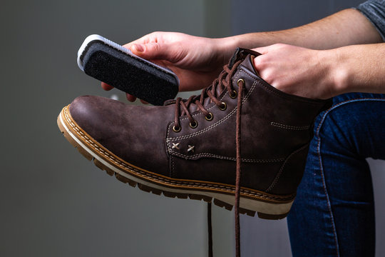 A person is cleaning men's suede casual boots with brush. Shoe shine and care.  Footwear moisture and dirt protection