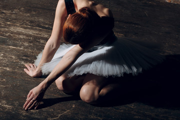 Young beautiful woman ballet dancer, dressed in professional outfit, pointe shoes and white tutu.