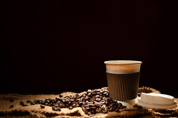 Paper cup of coffee and coffee beans on black background