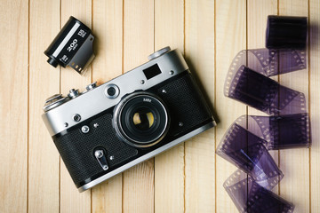Old film camera with film on wooden boards top view