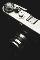 Old vintage film camera on black background close-up, high contrast, vertically