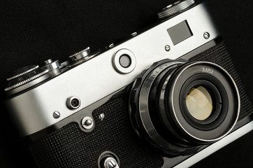 Old vintage film camera on black background, close-up, high contrast