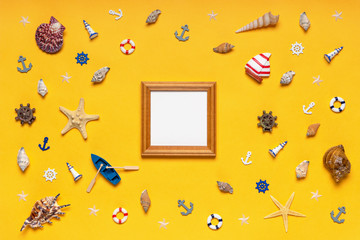 Round frame made of decorative items and miniature toys: seashells, seastars, vessel, boat, anchors, steering wheels, life buoys. Empty wooden photoframe, mock-up. Summer vacation, sea travel concept