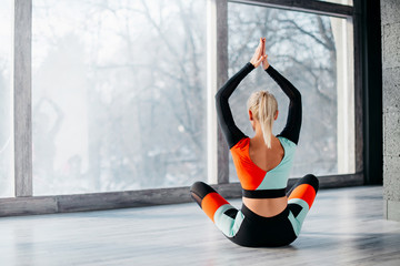 young woman practicing yoga in fitness studio