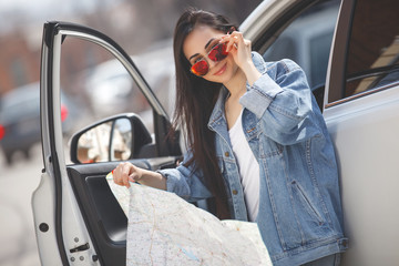 Young woman holding map of the city. Attractive girl on the car travel. Driver with map.