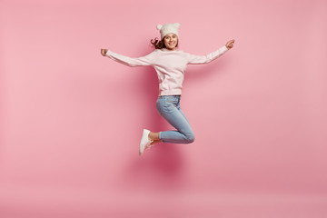 Full length shot of pleased fit girl has high jump in air, wears warm white hat with ears, sweatshirt, jeans and sneakers, spreads hands, isolated over pink background, hears pleasant music.