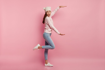 Sideways shot of surprised young European woman shapes big huge object with hands, demonstrates something large, wears stylish hat, sweatshirt, jeans, raises leg, models against pink background Wall mural
