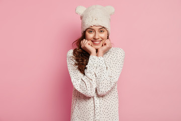 Photo of attractive young European woman keeps hands under chin, has toothy smile, dressed in polka dot shirt, poses against pink background, expresses satisfaction, feels enjoyment and pleasure