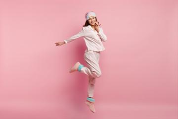 Indoor shot of overjoyed European woman raises leg, spreads hand, wears casual pyjamas and eyemask,...
