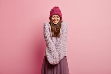Positive Caucasian young female model keeps hands together, wears long sleeved knitted sweater, pink hat, closes eyes from pleasure, models over rosy background. People and emotions concept. Wall mural