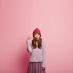 Photo of stunned beautiful woman with amazed facial expression, dressed in jumper and skirt, points above, poses over pink background, shows free space for your advertising content or slogan