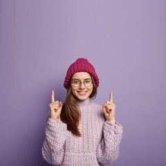 Vertical shot of European woman with gentle smile, wears warm knitted headgear and jumper, points above, wears round spectacles, advertises something over purple background. People and season