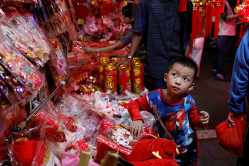 Boy takes a look at souvenirs at a traditional market ahead of the Chinese Lunar New Year in Jakarta