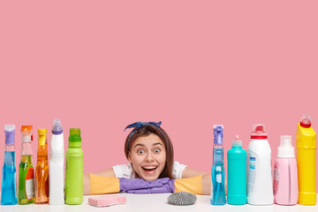 Pretty young woman with dark hair, smiles broadly, wears rubber protective gloves, leans on table with cleaning supplies, isolated over pink background, happy to finish washing. Blank space for text