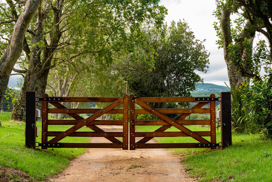 Wooden gates to a tree lined avenue.