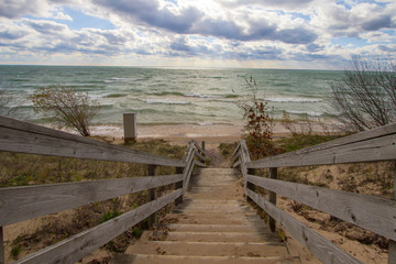 Wooden Stairs To Beach. Long wooden staircase leads to a sunny sandy beach on the Michigan coast of Lake Michigan.