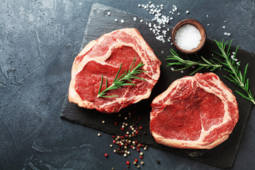 Fresh meat on slate black board top view. Raw beef steak and spices for cooking. Wall mural