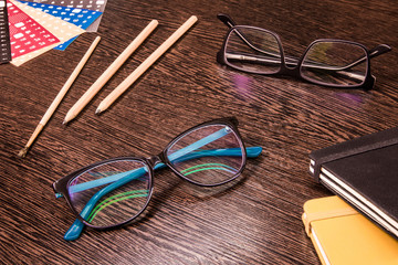 Two pairs of glasses with pencils, notebooks and stickers on the table. Study concept