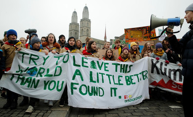 Participants display banners during a demonstration against climate change in Zurich