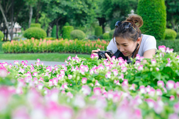Female photograph with camera taking a picture of  flowers