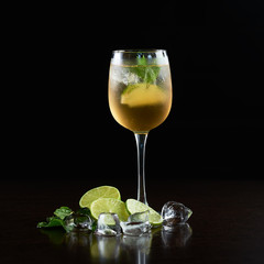 Elegant crystal cocktail glass with cold summer refreshing juicy drink, thin slices of lime, fresh green mint leaves and transparent ice cubes isolated on black background. Picture aspect ratio 1:1