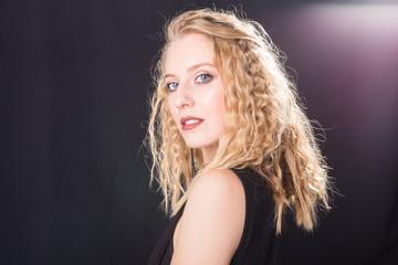 Portrait of sexy blond elegant woman in black dress standing on black background
