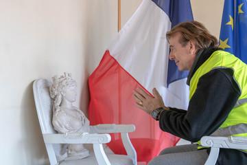 Gilet jaune suppliant Marianne symbole de la République française de l'écouter durant la consultation nationale