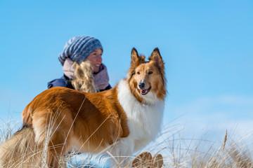 Junge Frau am Strand mit einem Hund.