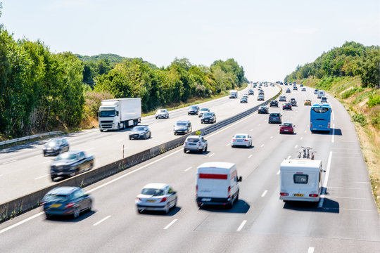 Heavy but fluid traffic on the eight-lane A10 highway in France in the direction of Bordeaux by a hot summer day with cars, vans, trailers, buses and semitrailer truck driving.