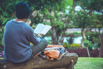 The young man was reading a book at the park. Among the natural trees and beautiful flower garden