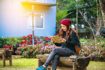 The girl smiled and was happy with the book she read. Read a book in the flower garden..