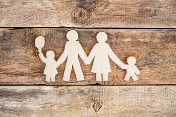 Paper family over wooden background