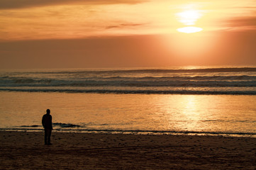 Silhouettes at sun set on the main beach of Agadir