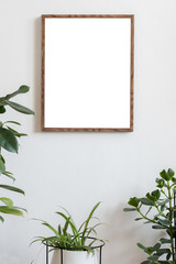 Scandinavian and botanical interior with brown mock up poster frame on the white wall. White backgrounds walls. Modern and floral concept. Nature lover.