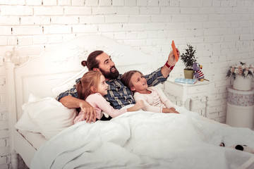 Delighted joyful man taking selfies with his daughters