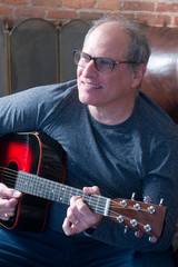 middle age senior man playing guitar