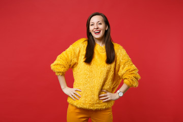 Portrait of laughing pretty young woman in yellow fur sweater standing with arms akimbo isolated on bright red wall background in studio. People sincere emotions lifestyle concept. Mock up copy space.
