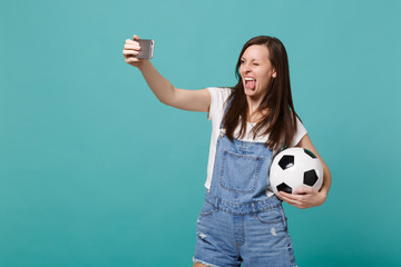 Funny young girl football fan with soccer ball doing selfie shot on mobile phone showing tongue isolated on blue turquoise background. People emotions sport family leisure concept. Mock up copy space.