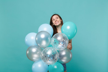 Portrait of cute dreamful young woman in denim clothes looking up celebrating holding colorful air balloons isolated on blue turquoise wall background. Birthday holiday party, people emotions concept.
