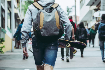 Teen walking and skateboarding through the streets of a urban city in a cloudy day enjoying the moment and having fun, boys with a skate and backpack visiting a modern town in the weekend. Trendy boy