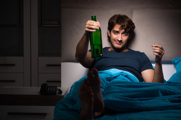 Man drinking in the bed under stress