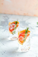 Alcoholic cocktail with grapefruit, soda, ice, gin and rosemary