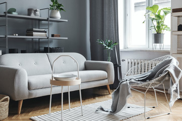 Modern and scandinavian living room with design sofa, coffee table, plants, stylish accessories and bookstand on the grey wall. Brown wooden parquet. Concept of minimalistic and elegant interior.