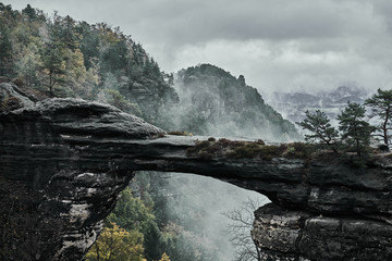 Misty foggy landscape of the Pravcicka gate (Pravcicka brana) the largest natural sandstone arch in Europe in Czech Switzerland (Bohemian Switzerland or Ceske Svycarsko) National Park