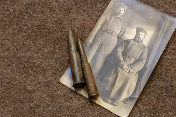 Photo of two soldiers in period of World War I and rifle bullets on trench coat WW1