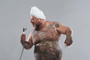 Enthusiastic tattooed man using shower head as his microphone