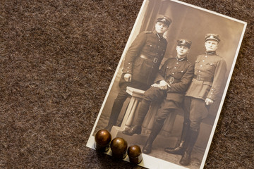 Three Latvian soldiers in period before World War II (1935) and pistol bullets on trench coat